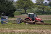 Farmworkers removing a salad crop row cover onto a tractor spool on a farm in Warwickshire - John Harris - 2010,2010s,agribusiness,agricultural,agriculture,BAME,BAMEs,BME,bmes,capitalism,capitalist,crop,crops,Diaspora,diversity,driver,drivers,driving,EARNINGS,eastern European,eastern Europeans,EBF,Economic