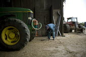 A farmworker maintaining machinery in a farmyard Wormleighton, Warwickshire - John Harris - 2010s,2012,agricultural,agriculture,by hand,capitalism,capitalist,EARNINGS,EBF,Economic,Economy,employee,employees,Employment,EQUALITY,farm,Farm Worker,farm workers,farmed,farmer,farmers,farmhand,farm