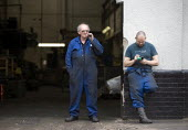Workers at an engineering factory take a fag break outside. Digbeth, Birmingham. - John Harris - 2010s,2012,break,break time,CELLULAR,CIGARETTE,cigarettes,communicating,communication,DINNER,dinners,DINNERTIME,employee,employees,Employment,engineer,engineers,FACTORIES,factory,job,jobs,LAB,LBR,lunc