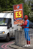 Young human billboard dressed up in Spiderman costum holding a board advertising Domino's medium Pizza for �5 on a street corner, Birmingham - John Harris - 24-05-2012