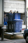 A lorry driver operating a tailgate lift on a lorry collecting confidential office paper waste in a locked and secure wheelie bin for off site shredding. Birmingham. - John Harris - 27-07-2012