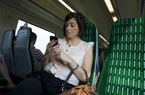 Passenger texting on her mobile phone, train journey from Stratford upon Avon to Birmingham. - John Harris - 27-07-2012