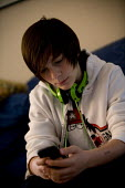 Teenager with headphones and Ipod, texting on his blackberry at home. - John Harris - 13-07-2012