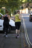 Women jogging along the pavement as a white van pulls out infront of them, Cheltenham - John Harris - 31-08-2012