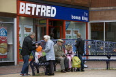 Shoppers in Bilston outside Betfred, the bonus king, Wolverhampton - John Harris - 2010s,2012,adult,adults,AGE,ageing population,bag,bags,Betting Shop,bought,buy,buyer,buyers,buying,cash,child,CHILDHOOD,children,cities,city,City centre,commodities,commodity,communicating,communicati