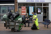 Wolverhampton city council street cleaners as an unemployed man looks on, Bilston, Wolverhampton - John Harris - 2010s,2012,bag,bags,bin bag,bin bags,binbag,binbags,black,by hand,cities,city,City centre,cleaner,cleaners,cleaning,cleansing,collection,council,Council Workers,EARNINGS,employee,employees,Employment,