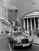 A Rolls Royce Silver Shadow on Threadneedle Street in the City of London. Bank of England, Stock Exchange, Nat. West. Tower, and Royal Exchange. - John Harris - 09-06-1982