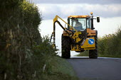 A farmworker Hedge cutting with a tractor-mounted hedge trimmers or reach flail mower, on a road by Meon Hill, Warwickshire - John Harris - 27-01-2010