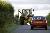 A car passing a farmworker Hedge cutting with a tractor-mounted hedge trimmers or reach flail mower, on a road by Meon Hill, Warwickshire - John Harris - 27-01-2010