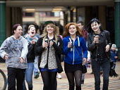 Teenage girls singing as they walk through the shopping precinct (drinking Monster energy drinks) Broadgate shopping precinct, Coventry - John Harris - 17-11-2012