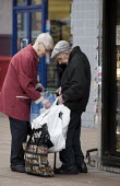 An elderly couple struggling with their weekly shopping bags, Broadgate shopping precinct, Coventry - John Harris - 2010s,2012,adult,adults,age,ageing population,BAG,bags,bought,buy,buyer,buyers,buying,Carrier Bag,cities,city,City centre,commodities,commodity,consumer,consumers,couple,COUPLES,customer,customers,EBF
