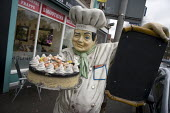 A life size restaurant chef mascot made of plaster with a cake and a blackboard menu outside a cafe, Coventry - John Harris - 17-11-2012