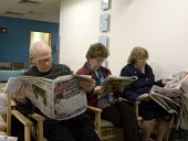 Elderly patient reading a newspaper whilst waiting to attend an appointment in the waiting room, Outpatient Ophthalmology Clinic, The Wrekin Community Clinic, Telford, Shropshire - John Harris - 13-11-2012