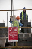 Bricklayer carrying a tub of mortar by a loading bay sign. Construction of new social housing, Stratford-upon-Avon, Warwickshire - John Harris - 2010s,2013,bays,bricklayer,bricklayers,bricklaying,Brownfield Site,builder,builders,building,building site,Building Worker,BUILDINGS,by hand,capitalism,capitalist,carries,carry,carrying,communicating,