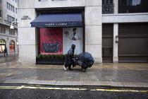 A homeless man pushing his belongings along the street past a Ralph Lauren clothing shop, Cork Street, Mayfair, London - John Harris - 13-04-2013