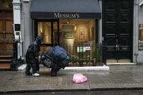 A homeless man pushing his belongings along the street past an art gallery, Messums art dealers, Cork Street, Mayfair, London - John Harris - 13-04-2013