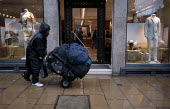 A homeless man pushing his belongings along the street past an exclusive clothing shop, Cork Street, Mayfair, London - John Harris - 2010s,2013,AFFLUENCE,AFFLUENT,apparel,BME black,Bourgeoisie,clothes clothing,clothing,deprivation,destitute,elite,elitism,EQUALITY,ethnic,ETHNICITY,excluded,exclusion,fashion,fashionable,fashions,HARD