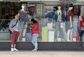 Shoppers and the shopwindow display with garments for �4 and �2.50. Primark Store, Coventry - John Harris - 2010s,2013,adolescence,adolescent,adolescents,apparel,bought,buy,buyer,buyers,buying,capitalism,capitalist,CELLULAR,cities,city,City centre,clothes,clothing,commodities,commodity,communicating,communi