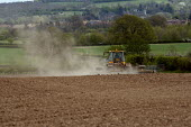 A farmworker using a cultipacker to form a seedbed in a field, Warwickshire - John Harris - 03-05-2013