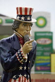 An Uncle Sam figure next to a BP petrol station, Norfolk. Uncle Sam was a national personification of the power of America and a nickname for the U.S. federal government Uncle Sam is derived from two... - John Harris - WW2,2010s,2013,ACE,American,americans,art,arts,artwork,artworks,brand,branding,capital,capitalism,capitalist,culture,Dandy,Doodle,driver,drivers,driving,EBF,Economic,Economy,figure,filling station,fla
