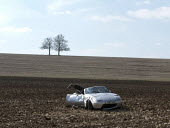 A sports car crash. A road traffic accident on a country lane B road. The vehicle left the road and the wreckage is in the middle of a field. Lighthorn, Kineton, Wawickshire - John Harris - 06-04-2013