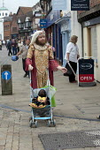 A man dressed as an Elizebethan queen dancing as he pushes a pushchair with a toy monkey. Stratford upon Avon. - John Harris - &,2010s,2013,ACE,arts,costume,costumes,culture,DANCE,DANCER,DANCERS,dancing,dressed up,dressing up,fancy dress,hea,health,holiday,holiday maker,holiday makers,holidaymaker,holidaymakers,HOLIDAYS,leisu