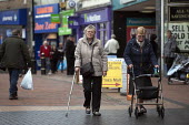 Pensioners, one with a walking stick, Dudley High St - John Harris - 2010s,2013,adult,adults,age,ageing population,bought,buy,buyer,buyers,buying,commodities,commodity,consumer,consumers,customer,customers,disabilities,disability,disable,disabled,disablement,elderly,FE