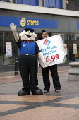 Danny Dominos pizza mascot and sandwich board carrier, walking advertisements infront of a 99p Store, Dudley High St. The figure is paid 5 per hour, the A board carrier 6.40. - John Harris - 17-06-2013
