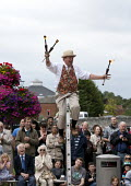 Street entertainers, Juggling fire sticks on a unicycle. Tourists visiting Stratford upon Avon, Warwickshire - John Harris - 24-08-2013