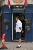 A restaurant worker taking a break outside a fish and chip restaurant, Stratford upon Avon, Warwickshire - John Harris - 24-08-2013