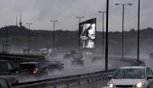 A Woman in an illuminated advertisement for Aussie Miracle Recharge Moisture Infuser Leave-in Conditioner and shampoo beside the M5 motorway, A heavy rain storm has made driving conditions hazardous w... - John Harris - 2010s,2013,ACE,advertisement,advertisements,advertising,AUTO,AUTOMOBILE,AUTOMOBILES,AUTOMOTIVE,beautiful,Beauty,bigotry,busy,car,cars,CLIMATE,conditions,cosmetic,cosmetics,culture,dark,DISCRIMINATION,