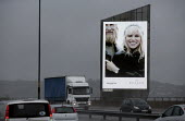 An illuminated advertisement showing a blonde couple with a watch by Skagen of Denmark, A heavy rain storm has made driving conditions hazardous with poor visibility. West Midlands - John Harris - 2010s,2013,ACE,adult,adults,advertisement,advertisements,advertising,AUTO,AUTOMOBILE,AUTOMOBILES,AUTOMOTIVE,car,Carat of Gold,cars,CLIMATE,conditions,consumer,consumerism,consumers,couple,COUPLES,cult