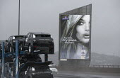 A Woman in an illuminated advertisement for Aussie Miracle Recharge Moisture Infuser Leave-in Conditioner and shampoo beside the M5 motorway as a car transporter carrying new Range Rover Evoque cars p... - John Harris - 2010s,2013,4x4,ACE,advertisement,advertisements,advertising,AUTO,auto industry,AUTOMOBILE,AUTOMOBILES,automotive,beautiful,Beauty,bigotry,car,Car Industry,carindustry,carries,carry,carrying,cars,CLIMA