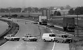 A police roadblock blocking the M 18 motorway to prevent TGWU dock worker pickets getting to Immingham docks to picket during the dock strike. The strike was called by the TGWUs national docks committ... - John Harris - 10-07-1984
