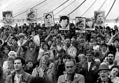 Applauding speeches. Holding up placards showing miners killed or imprisoned during the strike, Yorkshire miners Gala, Rotherham, Yorkshire - John Harris - 05-06-1985