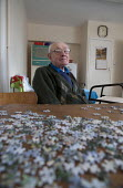 A pensioner at home, a Housing Association house. Stratford upon Avon, Warwickshire. - John Harris - 2010s,2014,adult,adults,age,ageing population,disabilities,disability,disable,disabled,disablement,elderly,EQUALITY,excluded,exclusion,fail,frailty,HARDSHIP,home,house,houses,housing,impoverished,impo