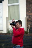 A photographer taking pictures of James Turner Street, featured in the Channel 4 program Benefits Street a tv series which has demonised the residents as the undeserving poor, Winson Green, Birmingham - John Harris - ,2010s,2014,Amateur Photographer,benefit,benefits,Birmingham,broadcast,broadcasting,camera,cameras,cities,city,communities,community,Demonisation,demonise,demonised,Demonization,demonize,demonized,Dom