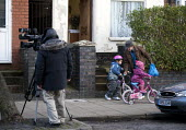 A parent and children, whilst an ITV camera crew film James Turner Street, featured in the Channel 4 program Benefits Street a tv series which has demonised the residents as the undeserving poor, Wins... - John Harris - ,2010s,2014,benefit,benefits,bicycle,bicycles,BICYCLING,Bicyclist,Bicyclists,BIKE,BIKES,Birmingham,boy,boys,broadcast,broadcasting,camera,cameraman,cameras,child,CHILDHOOD,children,cities,city,communi