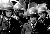 Police use riot gear for the first time in a strike. Miners mass picket as a convoy of coke lorries leave the plant for Scunthorpe Steelworks. Orgreave coke works, Miners strike Sheffield, South Yorks... - John Harris - 1980s,1984,adult,adults,Battle of Orgreave,British Steel,BSC,CLJ,coke works,coking plant,DISPUTE,DISPUTES,force,HAULAGE,HAULIER,HAULIERS,HGV,hgvs,INDUSTRIAL DISPUTE,leave,LGV,LGVs,lorries,LORRY,mass,m