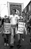 A striking miner with his two sons, Stoke on Trent, Staffordshire - John Harris - 1980s,1984,activist,activists,CAMPAIGN,campaigner,campaigners,CAMPAIGNING,CAMPAIGNS,DEMONSTRATING,demonstration,DEMONSTRATIONS,disputes,INDUSTRIAL DISPUTE,member,member members,members,miner,MINERS,MI
