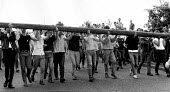 Pickets carrying a telegraph pole try to block the road to impead police charges by mounted and short shield riot police. Mass picket, Orgreave coke works, Yorkshire - John Harris - 29-05-1984