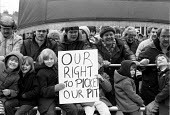 Miners, their wives and children march with their union banner to the pit. Picket of Frickley colliery in defiance of a court injunction limiting the number of pickets to 6, South Elmsall, Yorkshire.... - John Harris - 1980s,1985,at,collieries,colliery,court,DISPUTE,DISPUTES,INDUSTRIAL DISPUTE,injunction,member,member members,members,mine,MINER,Miners,MINER'S,miners strike miner's strike NUM,miner's strike the miner