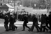 Some of the 27 scabs (out of 1200 miners) crossing the road from the washery as pickets look on, Silverwood colliery, Yorkshire - John Harris - 15-02-1985
