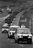 Police leading a convoy of lorries bring coke from Orgreave Coking works in Yorkshire to BSC Scunthorpe steelworks. M1 Yorkshire - John Harris - 1980s,1984,adult,adults,AUTO,AUTOMOBILE,AUTOMOBILES,AUTOMOTIVE,British Steel,BSC,CAR,cars,CLJ,disputes,force,HAULAGE,HAULIER,HAULIERS,HGV,hgvs,INDUSTRIAL DISPUTE,LGV,LGVs,lorries,lorry,MATURE,member,m