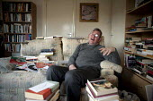 John, a disabled schizophrenic who hears voices, at home with his books which he reads avidly. His benefits have been reduced by the bedroom tax as his flat has a spare room. Stratford upon Avon, Warw... - John Harris - 2010s,2014,adult,Adult Education,adults,alone,bedroom,BEDROOMS,benefit,benefits,BOOK,books,CONFUSED,confusion,disabilities,disability,disability living allowance,disable,disabled,disablement,dla,edu,e