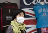 Japanese tourist wearing a face mask to protect herself from air pollution, Stratford upon Avon, Warwickshire. A smog cloud of dust from the Sahara mixed with car exhaust and industrial pollution from... - John Harris - 2010s,2014,Air Quality,alert,asian,asians,breathing,degradation,dust,eni,environment,Environmental,environmental degradation,Environmental Issues,flag,flags,hazard,hazardous,HAZARDS,holiday,holiday ma