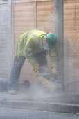 Cutting paving with a hand-held power saw. Contractors replacing a telegraph pole for BT. - John Harris - 01-04-2014