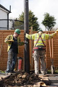 Contractors replacing a telegraph pole for BT. - John Harris - 2010s,2014,British Telecom,BT,crane,cranes,EBF,Economic,Economy,employee,employees,Employment,engineer,engineers,job,jobs,lbr,lifting,lowering,maintaining,maintenance,pavement,people,repair,repairing,
