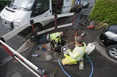 Workers installing a water meter in the pavement outside a house. - John Harris - 01-05-2014