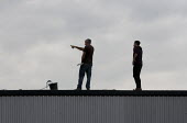 A worker clearing a industrial unit roof of debris, without a safety harness. - John Harris - 2010s,2014,building,Building Worker,buildings,clearing,communicating,communication,Construction Industry,conversation,conversations,dialogue,discourse,discuss,discusses,discussing,discussion,EBF,Econo